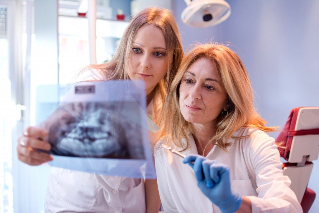 Dentists looking at teeth x-rays