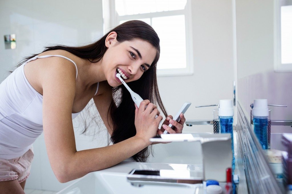 Woman brushing her teeth while using her smartphone