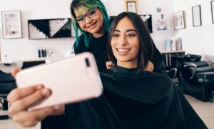 Woman taking a photo of her newly cut hair