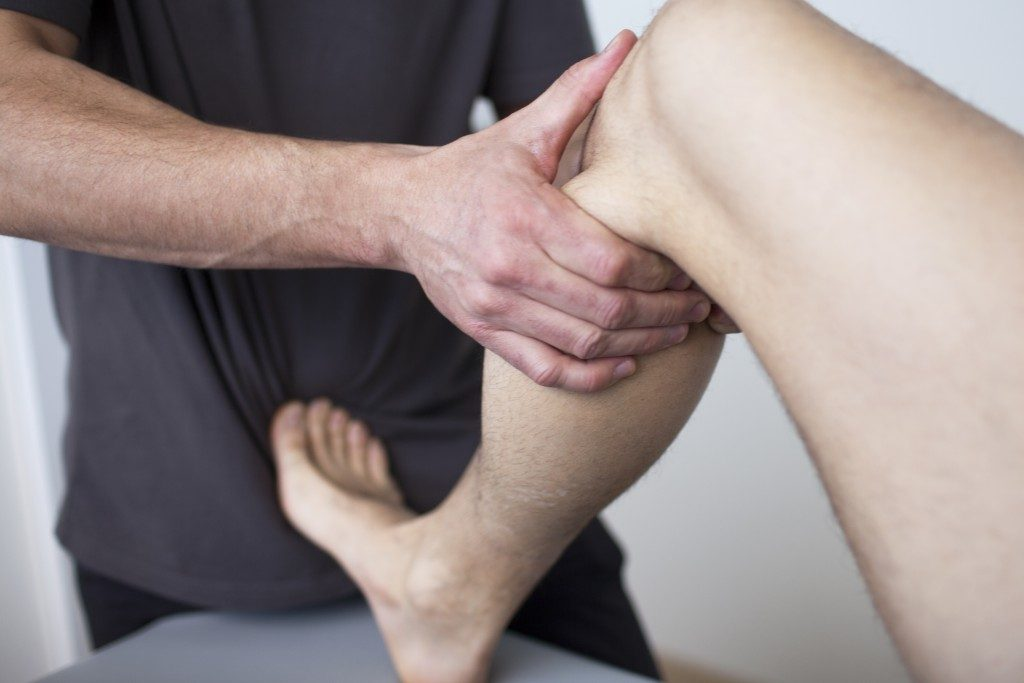 Physiotherapist cracking a leg