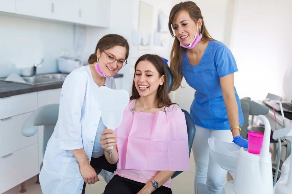 woman checking her teeth at the dentist clinic