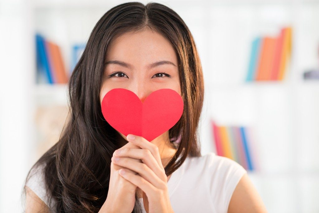 woman holding a heart over her mouth
