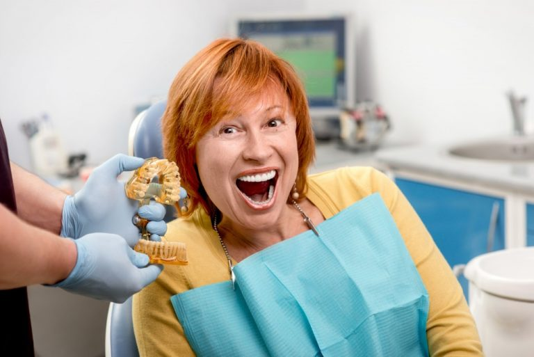 Smiling senior woman with new dental implants sitting in the dental office
