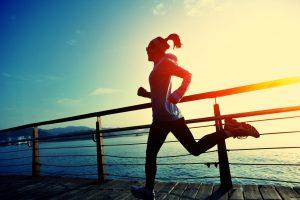 woman running on wooden boardwalk sunrise seaside