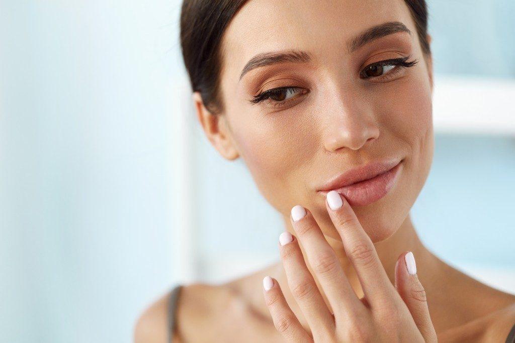 woman putting lip balm on dry lips