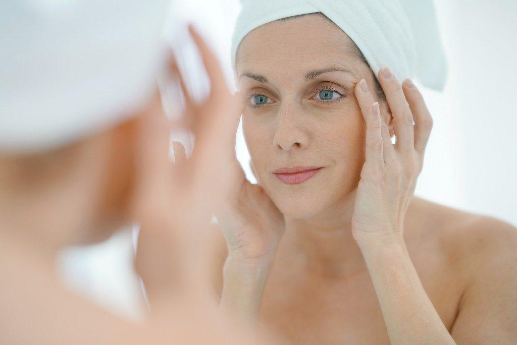 woman putting face cream