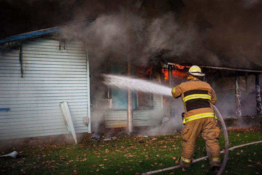 a firefighter putting out the fire of a house