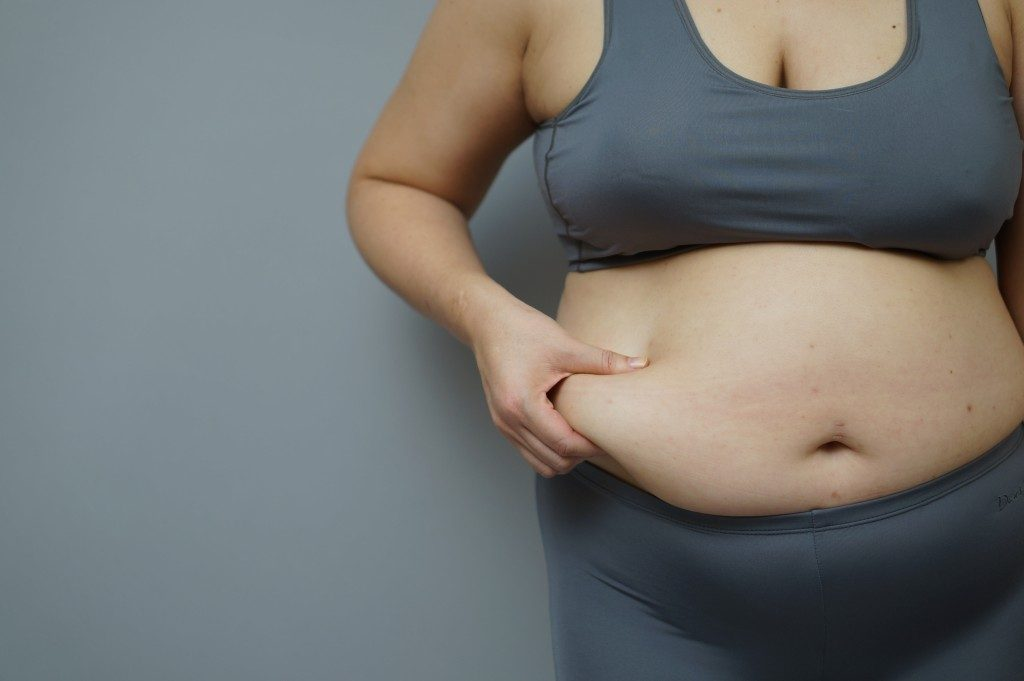 overweight woman pinching her stomach