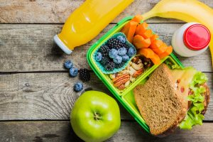 green lunch box full of fruits and vegetables