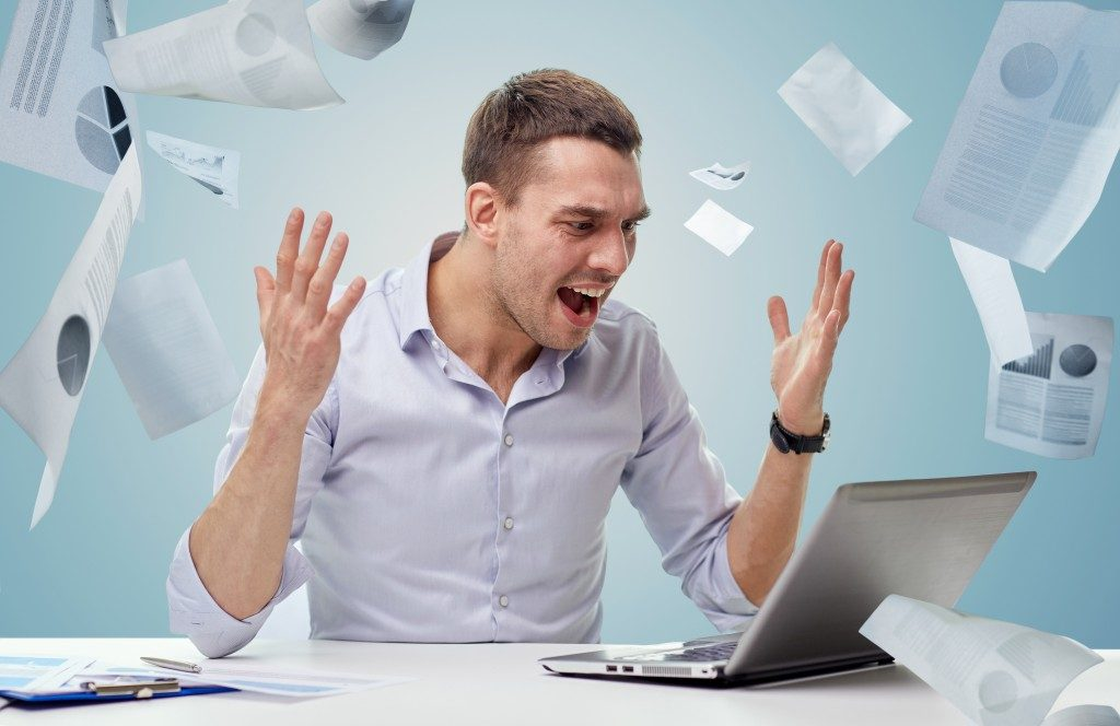 Angry businessman with laptop computer shouting over blue background and falling papers