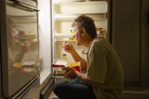 guy eating in front of a fridge