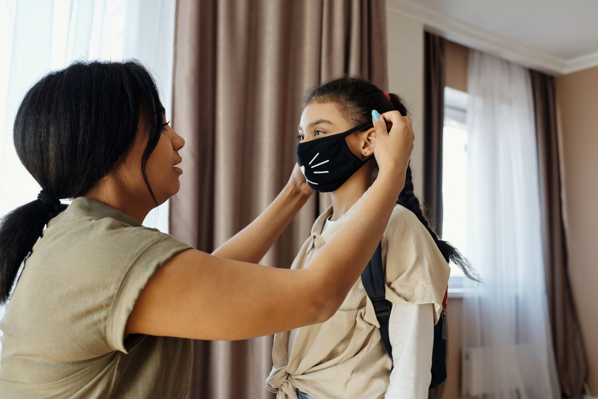 woman putting face mask with cat whiskers on child